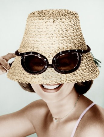 Woman wearing hat with fake sunglasses