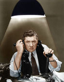 Man using two telephones