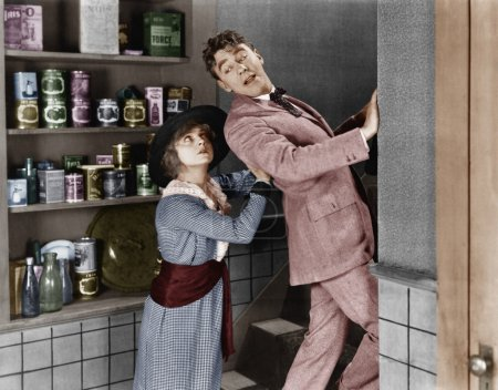Profile of a young woman pushing out a young man from a domestic kitchen