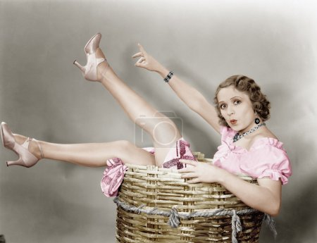 Young woman sitting in a basket looking surprised