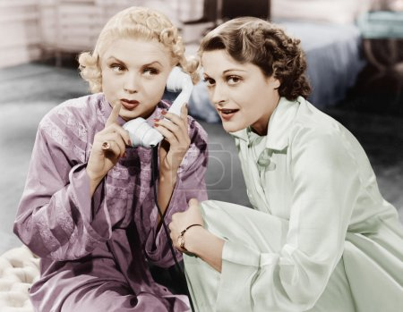 Two women sitting together and listening on the telephone receiver