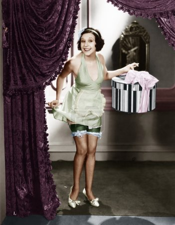 Woman walking into a room wearing lingerie and holding a hat box